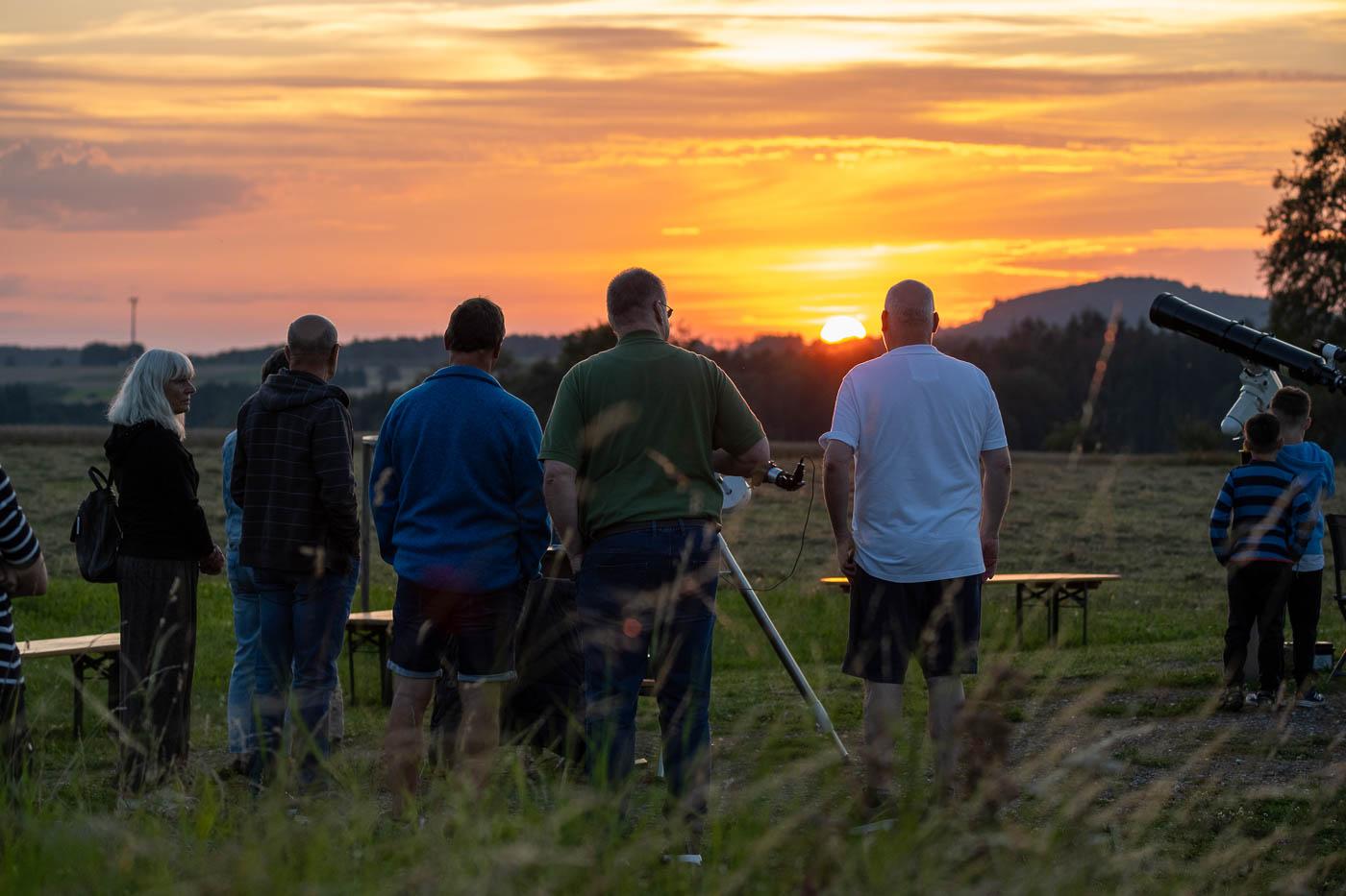 Menschen betrachten den Sonnenuntergang